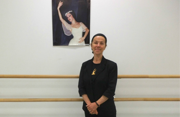 Jeunesse Classique Ballet Society's Founder & Artistic Director Umran Sumen, standing beside a portrait of herself from when she was a leading soloist with The National Ballet Company of Turkey.